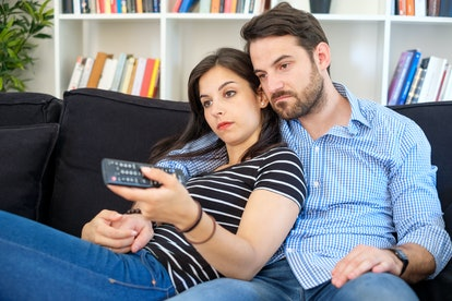 Lazy and bored couple at home sitting on sofa watching tv