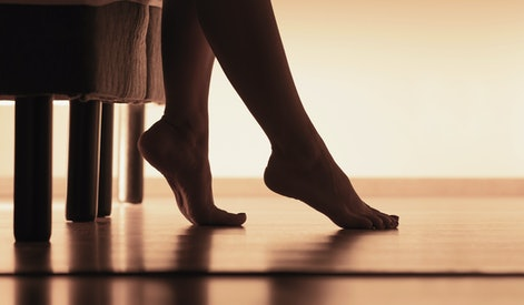 Female feet on hardwood floor. Young woman waking up and getting up from bed in the morning. Silhouette of legs and body in bedroom.