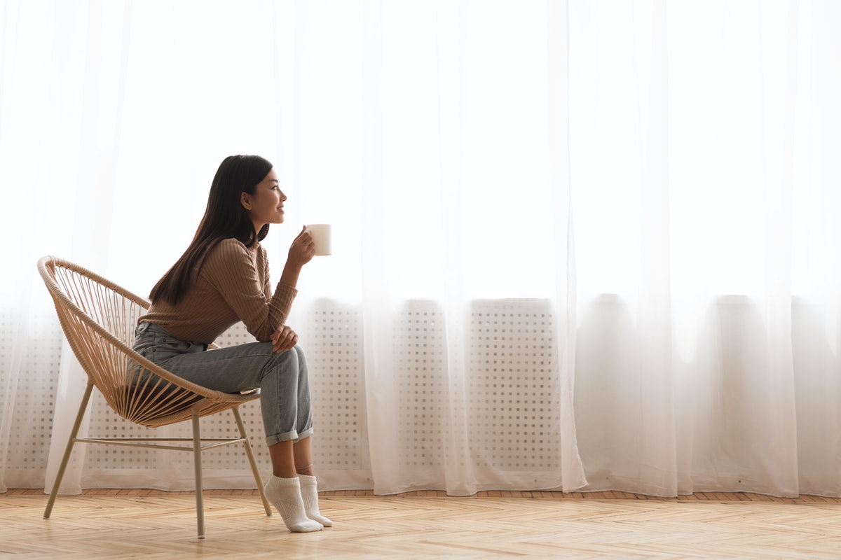 Young Girl Sitting In Modern Chair, Enjoying Coffee In Front Of Window, Side View