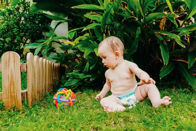 Baby sitting on the barefoot lawn playing with a colorful toy to stimulate his senses.