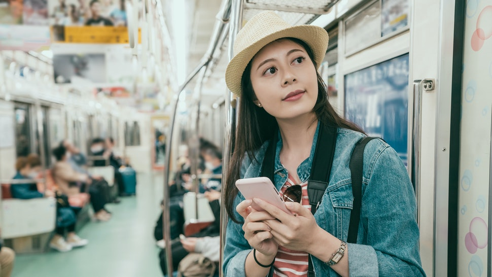 Young asian woman backpacker using smartphone in subway train. girl traveler smiling holding mobile phone texting online stand inside underground metro in quiet place look outside window to platform