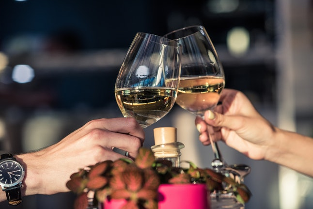 Young romantic couple with glasses of white wine on a date in a cozy Italian restaurant. Leisure, drinks, people and holidays concept - happy man and woman clinking glasses.