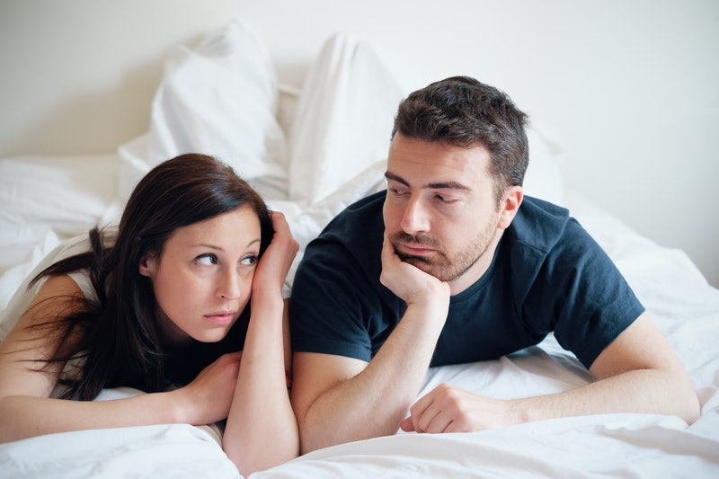 Worried and bored lovers couple after a fight lying in the bed