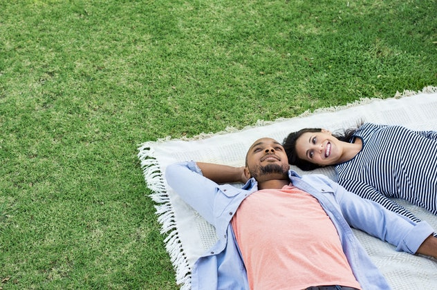 Young multiethnic couple lying on blanket on grass. Latin woman with her african boyfriend relaxing ...