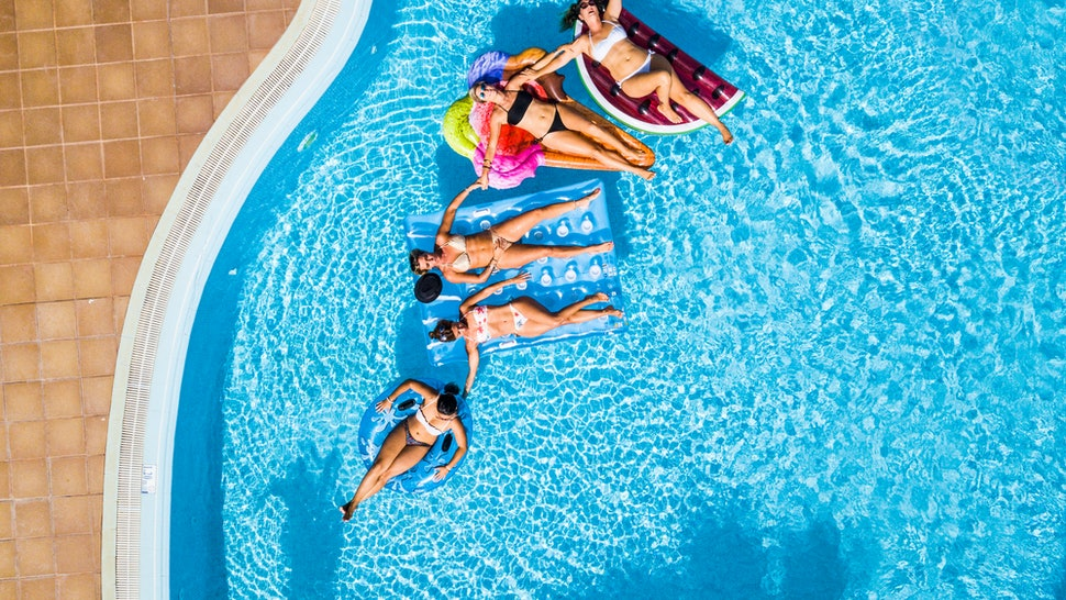 Coloured aerial background with group of friends woman caucasian people enjoying the summer holiday vacation at the blue water pool with trendy inflatable mattress lilos together with fun happiness