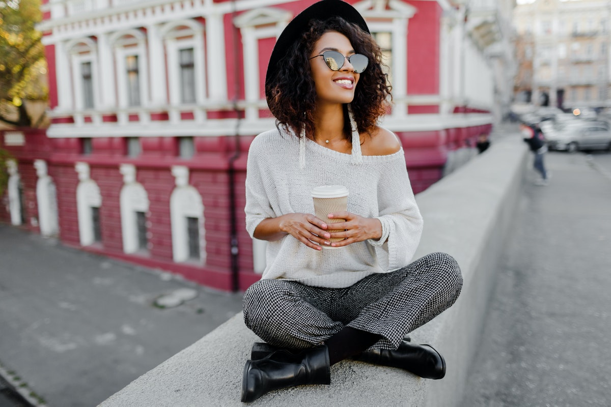 Street fashion look. Stylish black girl sitting on the bridge and holding cup of coffee or tea durin...