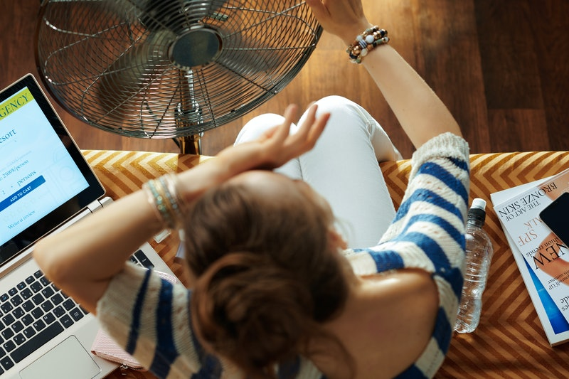 Upper view of elegant housewife sitting on couch in the modern house in sunny hot summer day cooling down using electric floor standing fan while suffering from summer heat.