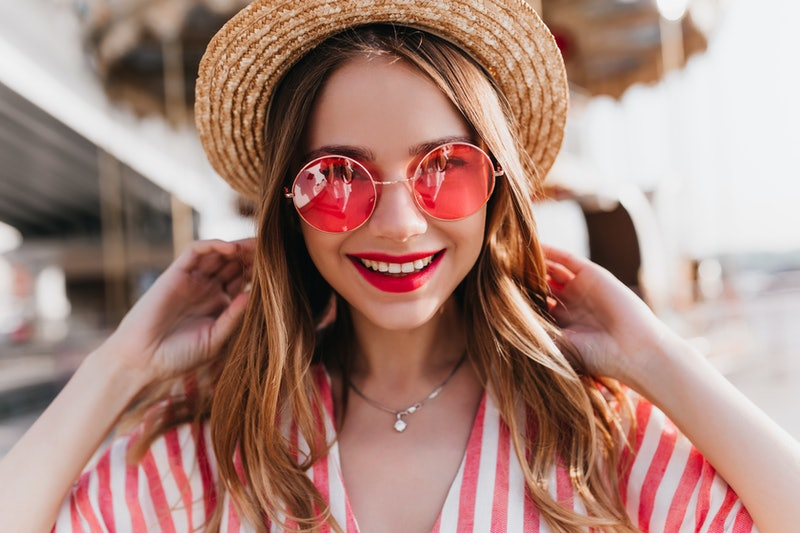 Portrait of sensual blonde woman wears trendy pink summer glasses. Outdoor photo of good-humoured lightly-tanned girl in straw hat.