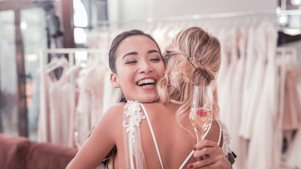 Wedding celebration. Joyful pleasant woman holding a glass with champagne while hugging her best friend