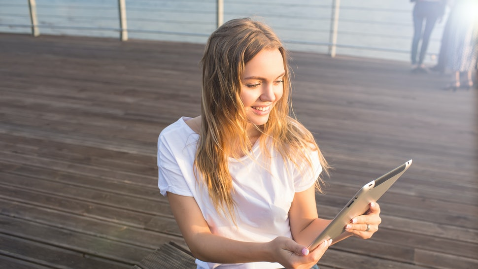 Happy smiling woman online ordering via portable touch pad while relaxing on embankment during recreation time in weekend. Joyful female watching funny video in social network via digital gadget