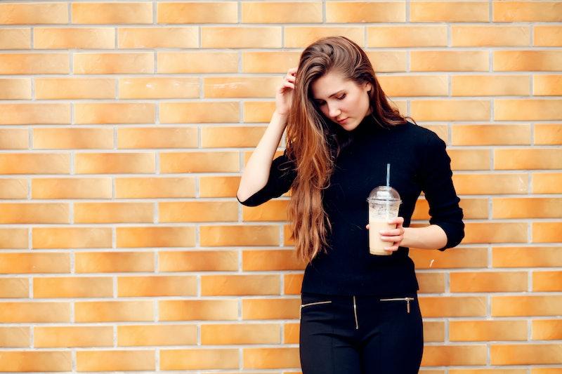 Happy beautiful girl drinking ice coffee in the street