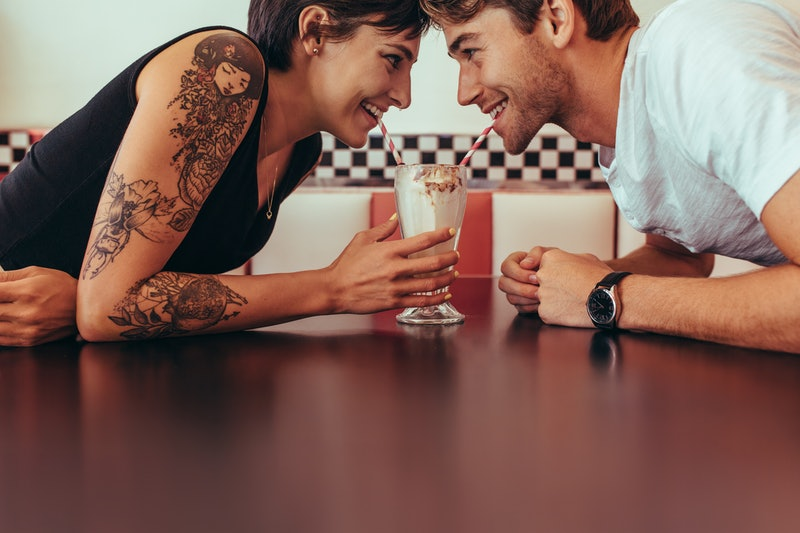 Close up of happy couple sharing a milk shake with straws sitting opposite to each other at a restaurant. Romantic couple sipping milk shake from a glass looking at each other.