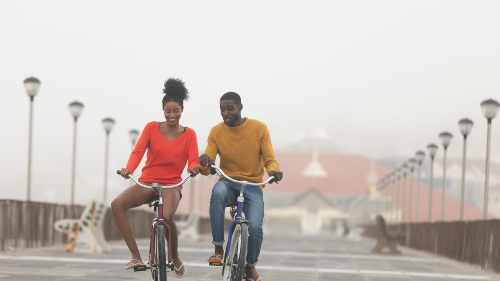 Front view of cute Multi-ethnic couple riding bicycle and having fun at promenade on a sunny day