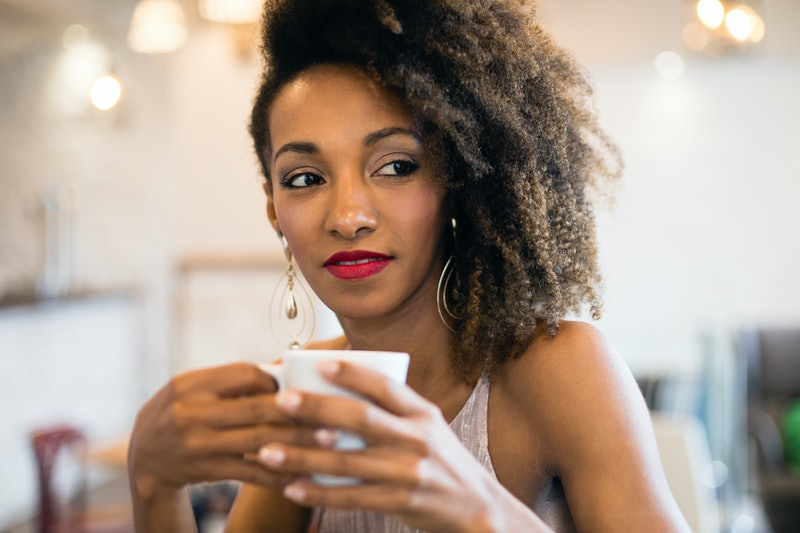 Stylish pensive black woman drinking a coffee in a cafe bar.