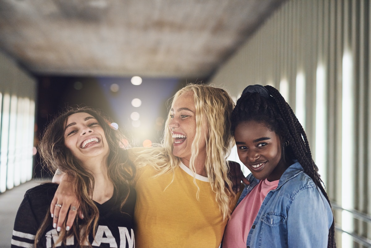 Laughing group of diverse young girlfriends having fun while walking together down a walkway in the ...