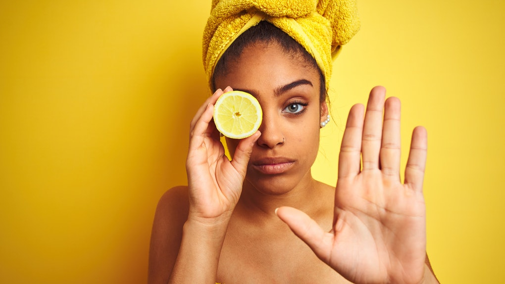 Afro woman wearing towel after shower holding slice lemon over isolated yellow background with open hand doing stop sign with serious and confident expression, defense gesture