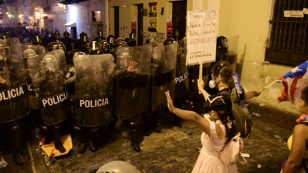 Demonstrators react in front of the police during clashes in San Juan, Puerto Rico, . Thousands of people marched to the governor's residence in San Juan on Wednesday chanting demands for Gov. Ricardo Rossello to resign after the leak of online chats that show him making misogynistic slurs and mocking his constituents