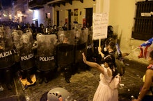 Demonstrators react in front of the police during clashes in San Juan, Puerto Rico, . Thousands of p...