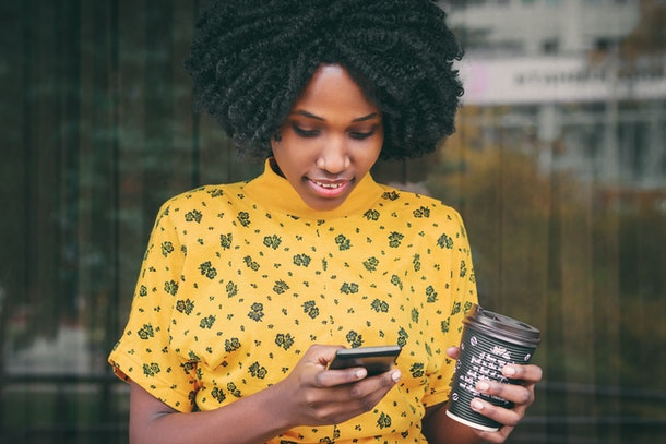 Young dark-skinned woman dressed in casual clothes holding cup of hot drink, enjoying coffee