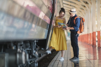 Couples travellers, read the map to plan travel on the platform in railway station.