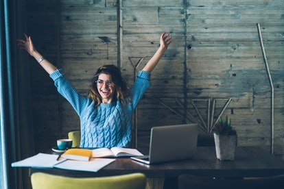 Student girl sitting at table with open notebook and raises hands up while smiling with sincere happiness. Woman overjoyed about successfully completed project on computer. Concept of achievement