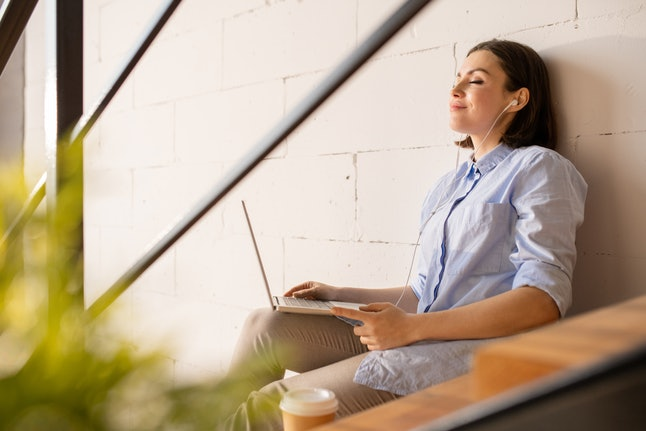 Happy young casual restful businesswoman with earphones and laptop enjoying her favorite music while sitting by wall