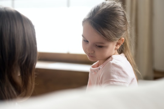 Focus on upset sad small daughter sitting on sofa with mother, mom scold kid for bad behaviour, child psychologist help girl deal with emotional social behavior problems trauma therapy support concept