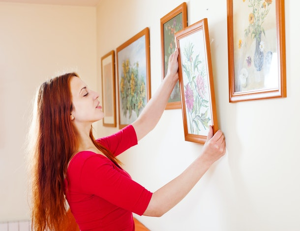 Long-haired woman in red hanging the  pictures on wall at home