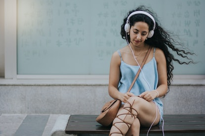 Woman listening to her headphones and texting.