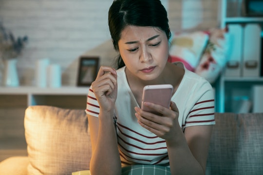upset sad skeptical unhappy serious asian woman talking texting on phone displeased with conversation at dark home in midnight. Negative human emotion face expression feeling using cellphone on couch