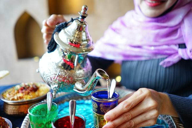 Female hand pouring Moroccan mint tea from traditional tea pot into a glass with blurred Chicken Biryani Rice on dining table. Ramadan food and drink preparation for iftar meal during the holy month.