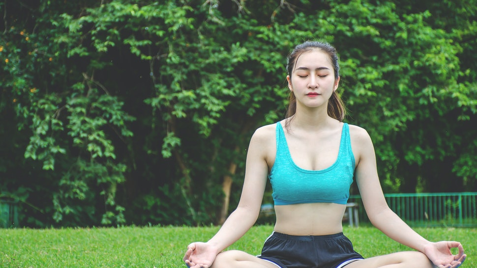 Woman meditating in a lotus yoga position on a yoga mat in the park