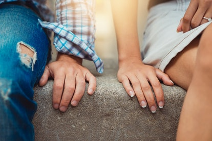 Hands of young couple in love close side by side on the first date. Loving couple has a happy relati...