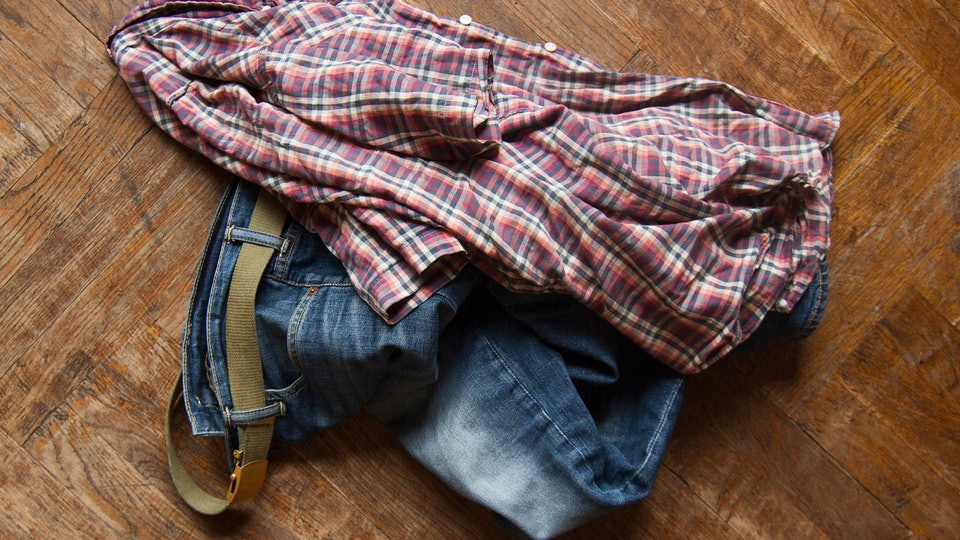 top view of man blue jeans and squared shirt thrown on the wooden floor