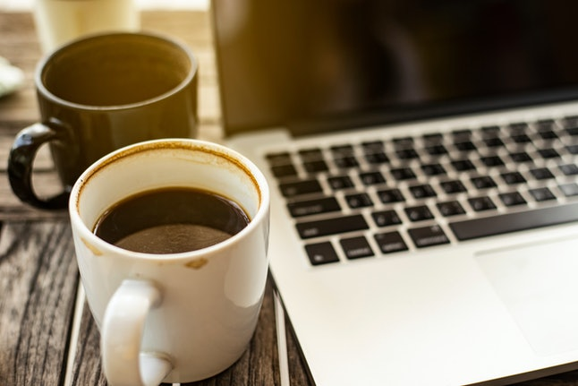 2 cups of coffee placed close to each other on the side of the notebook on the table.Business and Heavy work concept.
