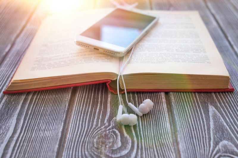 book, smartphone, headphones on a wooden background. audiobook. hobby. free time. recreation. literature.