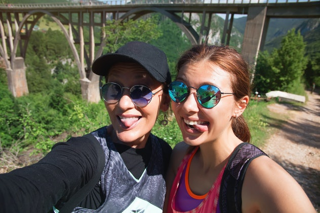 Travel hiking selfie self-portrait photo by happy couple on hike. Active lifestyle with hikers friends or lovers smiling at camera Morach,Beautiful senior mom and adult daughter are hugging, fun.