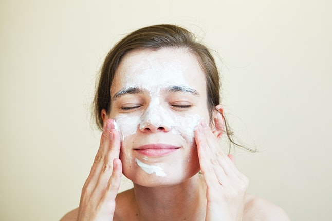 pretty young woman with clay mask on her face, facial care