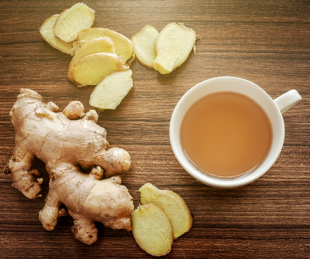 Ginger root and slices on wood background with a cup of ginger tea. Ginger tea helps warming the body in cold season, healthy drink. Soft light effect added.