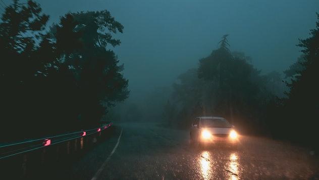 Car in the dark foggy road