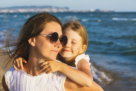 Happy mom and daughter smile at each other while walking near the sea on a warm sunny evening