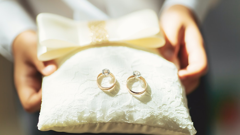 boy holds a magnificent pair of shiny golden wedding rings on a pillow