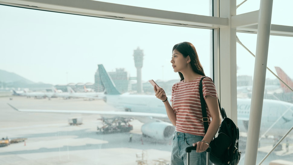 Young asian woman backpacker in airport waiting for airplane. japanese female holding mobile phone stand looking out window to runways in terminal hall carrying luggages.  Travel lifestyle concept.