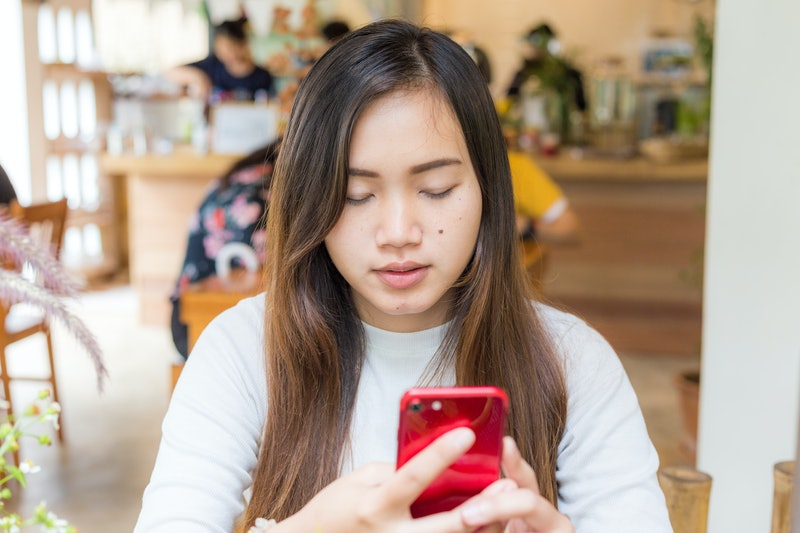 Busines casual women texting on smartphone sitting in cafe