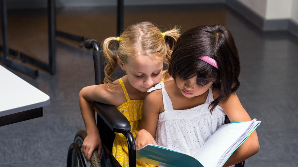 Cute girls sitting on wheelchair reading book in class room