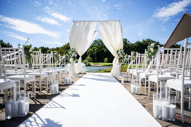 Beautiful wedding arch  and a rows of chairs for guests with the lake at background