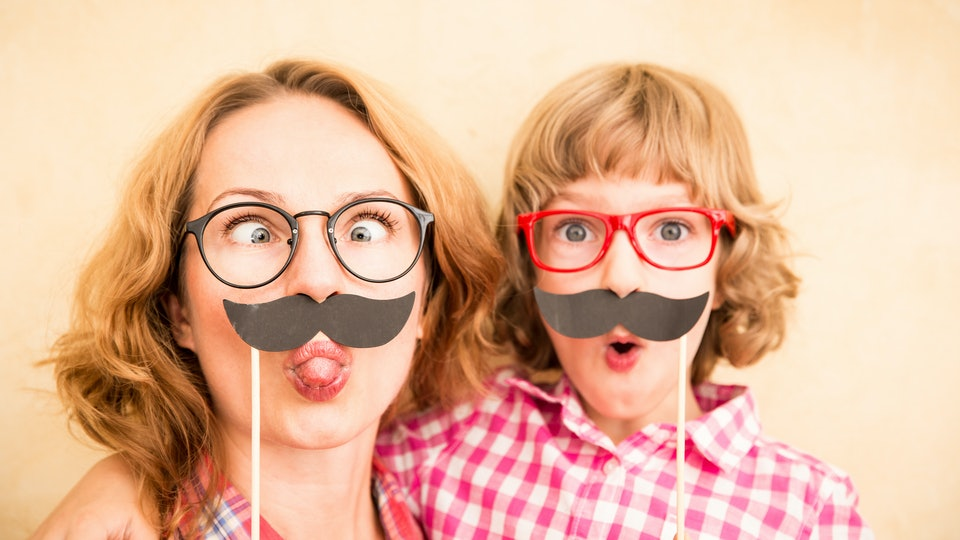 Mother and child with fake mustache. Happy family playing in home