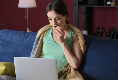 Beautiful young woman with laptop eating unhealthy food at night