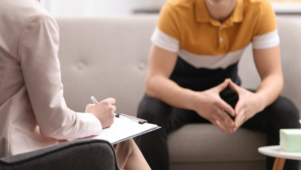 Psychotherapist working with young man in office, closeup