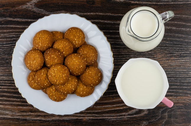 Heap of cookies with sesame in white plate, jug of milk, cup with milk on wooden table. Top view